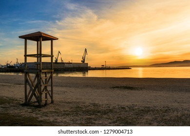 Wooden watchtower on Compostela beach in Vilagarcia de Arousa at orange sunset with harbor cranes at background