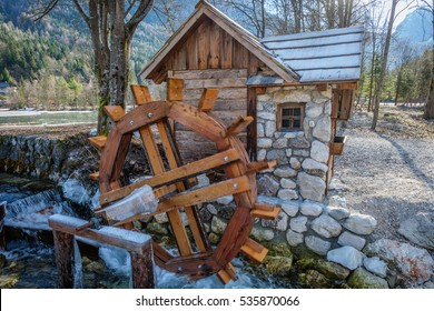 Wooden water wheel on a creek and a small house - mill next to it. Captured in Kranjska Gora, Slovenia.