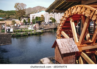 wooden water wheel in the village with clear water
