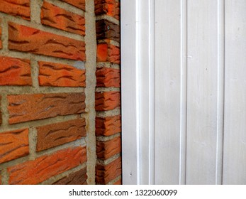 Wooden weatherboard painted white as a background and red brick wall corner
