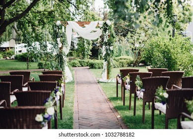 Wooden wedding arch  decorated by white cloth and flowers with greenery standing in the center of wedding ceremony. Brown chairs on side.