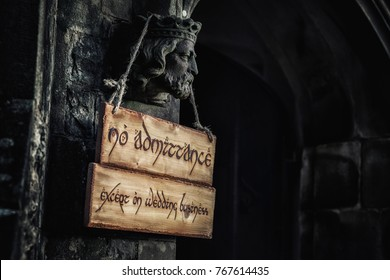 Wooden wedding business sign hanging from an old stone carved King head outside the church doorway