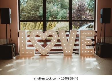 Wooden wedding love text on the floor. Decorative small light bulbs and heart shape love symbol.