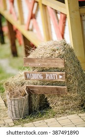Wooden wedding sign with indication of direction near small a stack of hay outdoor