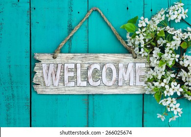 Wooden welcome sign with spring tree blossoms border hanging on antique teal blue wood background