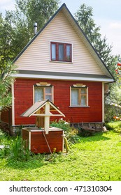 wooden well and simple country cottage in summer day