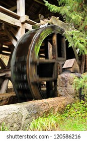 wooden wheel of an ancient water mill in motion