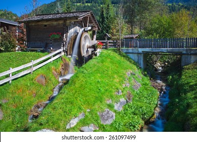 Wooden wheel of an ancient water mill in Dolomiti, water blurred by long exposition