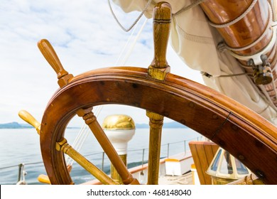 Wooden wheel of a big sailboat at sea. Close up nautical detail