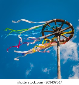Wooden wheel with bright ribbons on blue sky background. Slavic celebration of Midsummer