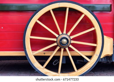Wooden wheel of a red classic style food wagon on the streets