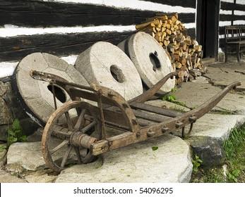 wooden wheelbarrow with three millstones in czech historical village,