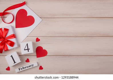 Wooden white background with red hearts, gifts, love envelope and wooden block calendar. The concept of Valentine Day. Top viev. Copy space for your text.