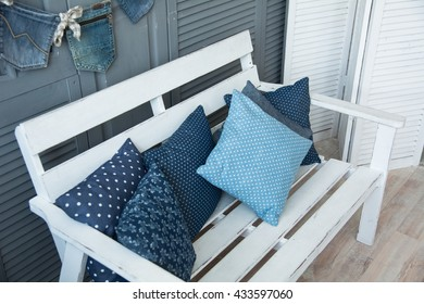 Wooden white bench with cushions for relaxing.