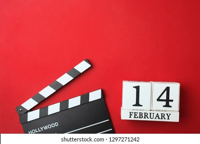 Wooden white calendar with date of February 14 and clapper on bright red background. Concept Valentine's day, filming. Top view, copy space.