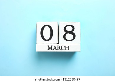 Wooden white calendar on blue background. Concept International Women's Day, March 8. Top view.