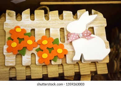 Wooden white decorative bunny with pink bow sits near the orange flowers of felt and a wooden small fence. Decor for the holiday of Easter. Easter concept, postkard.