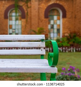 Wooden white garden bench with blurred background of orange wall with two huge windows at Montaza public park, Alexandria, Egypt