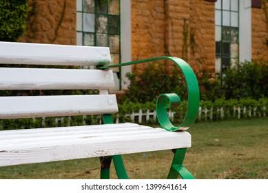 Wooden white garden bench with blurred background of orange bricks wall with windows at Montaza public park, Alexandria, Egypt