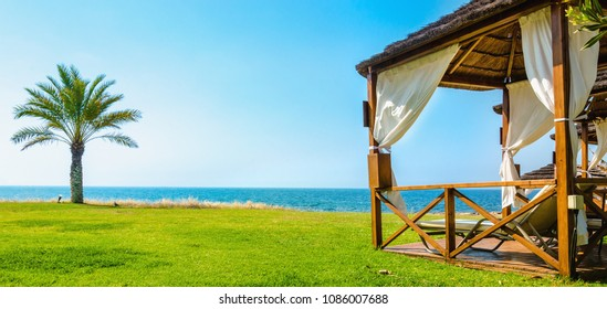 Wooden white gazebo with deck chairs and white curtains on luxury hotel on a sunny day