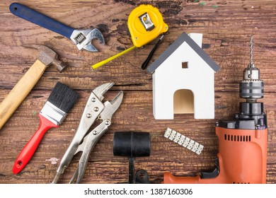 Wooden white house toy and construction tools on wooden background with copy space.Real estate concept, New house concept, Finance loan business concept, Repair maintenance concept