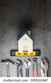 Wooden white house toy and construction tools on Gray-black cement floor background with copy space.Real estate concept, New house.Home repair concept
