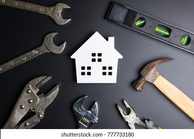 Wooden white house toy and construction tools on black background with copy space.Real estate concept, New house concept, Finance loan business concept, Repair maintenance concept