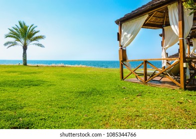 Wooden white pergola with deck chairs and white curtains on luxury hotel on a sunny day