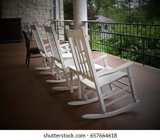 wooden white rocking chairs Three white rocking chairs lined up in a balcony of a building facing the garden