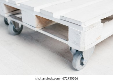 Wooden white short table with wheels staying on white floor