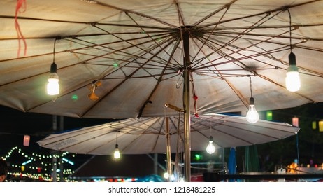 Wooden white umbrella at the night market in Chiang Mai. Kingdom of Thailand, South East Asia.