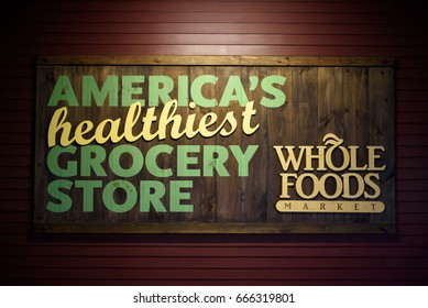 "Wooden Whole Foods Market sign with slogan ""America's healthiest grocery store"" at Ridge Hill shopping center, Yonkers, New York, Westchester, USA on June 25, 2017."
