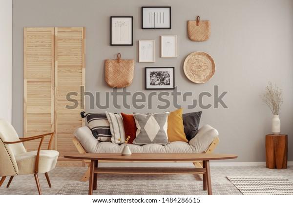 Accessoires en bois et osier dans le salon scandinave à la mode intérieur avec canapé futon avec oreillers