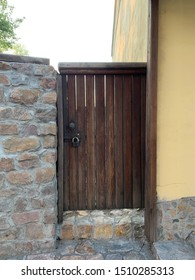 The wooden wicket between fence and stone wall. Stone fence and closed wicket to the house from brown wood with a handle and padlock