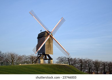 Wooden windmill in Bruges with blue sky in background