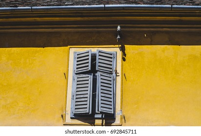 Wooden window against yellow wall in Sibiu, Romania