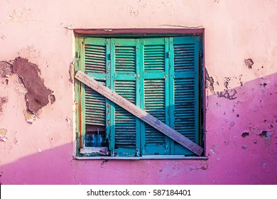 Wooden window, blue, pink stone house of the old buildings