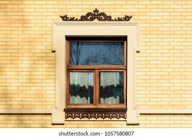 Wooden window of an elite country house of yellow brick, decorated frame with carved platbands