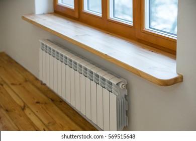 Wooden window. Heater radiators.  Wide wooden sill.