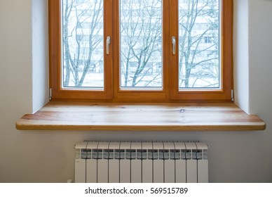 Wooden window. Heater radiators.  Wide wooden sill.
