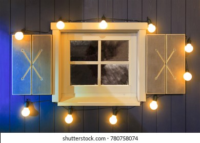 Wooden window of the house, decorated with a grill, burning lights. Christmas, New Year. Riga.