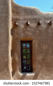 Wooden window of an Native American Adobe house in Sant Fe, New Mexico with wood beams, built of a material mix of earth and straw.