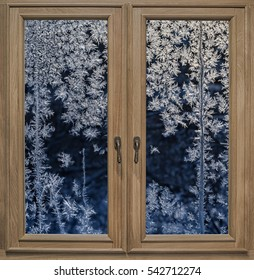 Wooden window and the night view through the frozen glass with an icy pattern