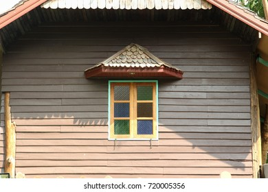 Wooden window on wooden house wall.