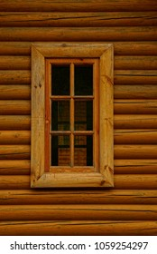 Wooden window on the wall of a house of brown logs