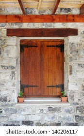 Wooden window in the stone wall of the house