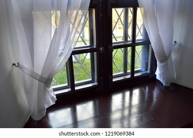 Wooden window with a wide window sill and white beautiful curtains, tulle.