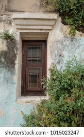 The wooden windows of the ancient building are sloping and there are plants on the walls.