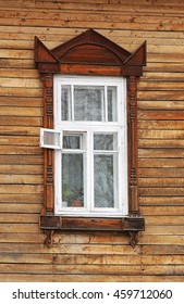 Wooden windows lacy architecture of old wooden houses in Tomsk, Siberia. Carved wooden brown decoration old building windows. The frame is white.