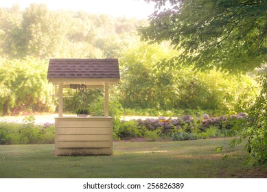 Wooden wishing well in clearing with trees, bushes in green background.